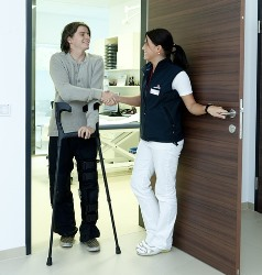 LPN greeting patient with crutches at door