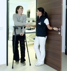 LPN greeting patient with crutches at door